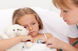 девочка лежит в кровати, ее осматривает врач